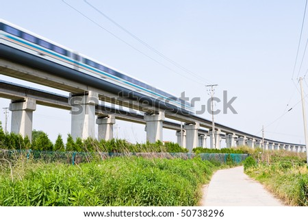 magnetic levitation (meglev) train travels at 431 km per hour through suburban shanghai, china - stock photo