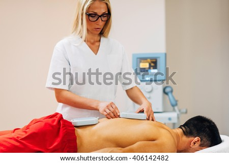 Magnetotherapy - Physical therapist placing magnets for treatment of patient's back - stock photo