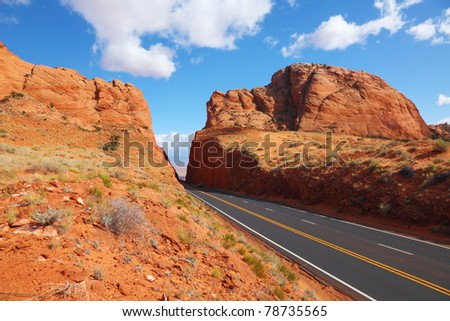 Magnificent American road among rocks of red sandstone - stock photo