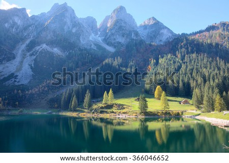 Magnificent autumn scenery of Lake Gosausee with rugged rocky mountain peaks in the background and beautiful reflections on smooth water, in Gosau, Austria ~ A fascinating nature scene of Alps, Europe - stock photo
