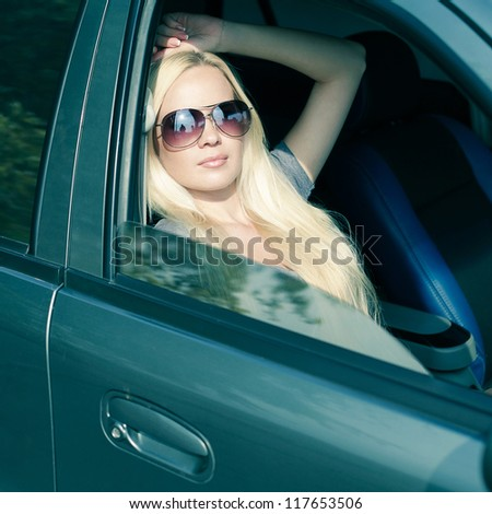 magnificent blonde girl with sunglasses sitting in blue colored car. outdoor shot - stock photo