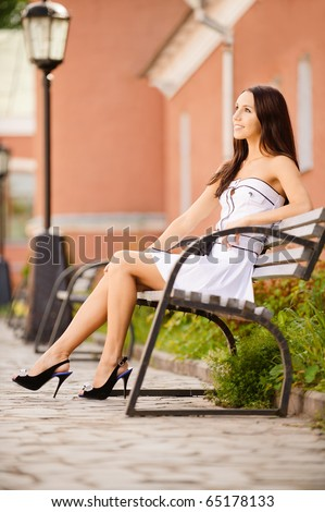 Magnificent brunette sits on bench which is on city street. - stock photo