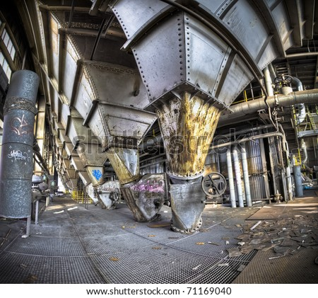 Magnificent colors melting together with the traces time left behind, this is what's left of the factory where people used to make a living one day. A shame vandals are now tagging the place. - stock photo