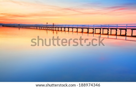Magnificent colours in the sky, pink towards the north and red towards the south, at idyllic Long Jetty Central Coast, Australia - stock photo