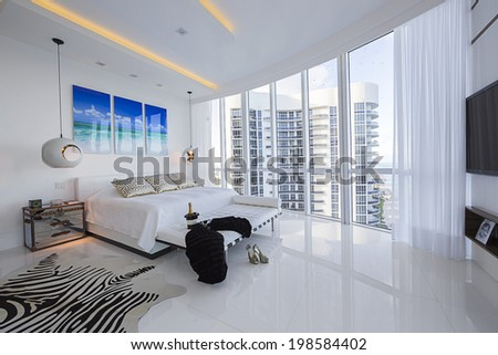 Magnificent contemporary master bedroom in white with ocean view. - stock photo
