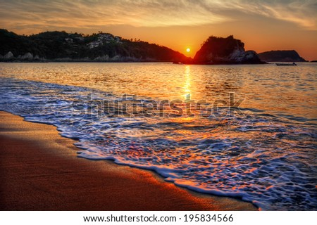 Magnificent dawn by a peaceful sandy beach with distant cliffs  - stock photo