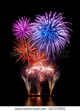 Magnificent fireworks display with happy colors on black background, reflected on water - stock photo