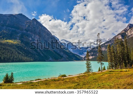 Magnificent Lake Louise is surrounded by mountain and glaciers. Rocky Mountains, Canada, Banff National Park. Great day - stock photo