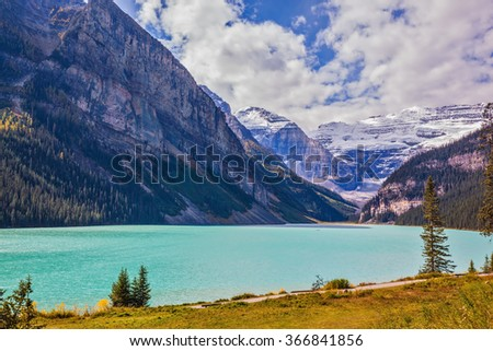 Magnificent Lake Louise is surrounded by mountain and glaciers. Rocky Mountains, Canada, Banff National Park. Great sunny day - stock photo