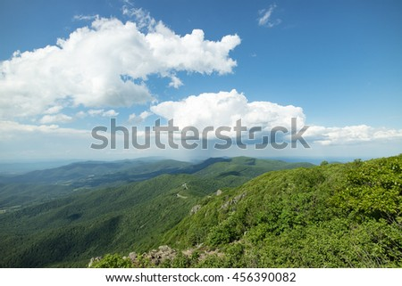 Magnificent landscape view of Shenandoah National Park and the Appalachian trail, surrounded by dense lush green forest under a blue sky with idyllic white clouds - stock photo