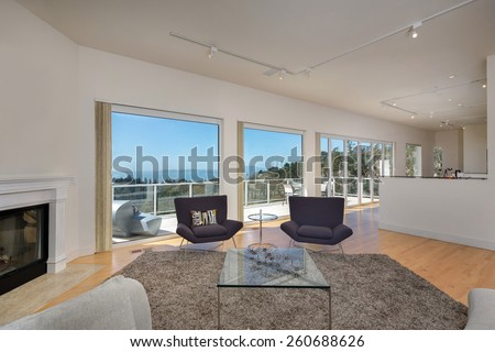 Magnificent living room in contemporary, modern home with large view window, balcony and fire place. Hardwood floor with hand-woven natural fine sisal rug, glass table, designer chairs in open space. - stock photo