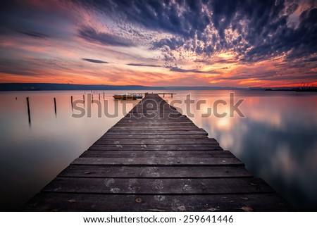 Magnificent long exposure lake sunset with boats and a wooden pier - stock photo