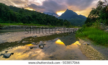 Magnificent mountain landscape river,forest and cloudy sky during sunset with mountain Nungkok and the majesty of mountain Kinabalu as background at Tambatuon village,Kota Belud,Sabah,Borneo.