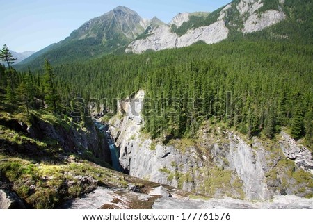 magnificent mountain landscape river, forest and cloudy sky in summer