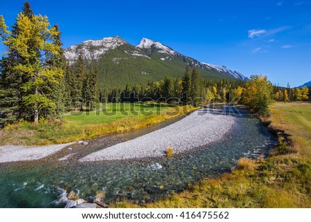 Magnificent picturesque valley in Banff National Park. Beneaped autumn stream with a pebbly bottom flows among fields and pine forests - stock photo