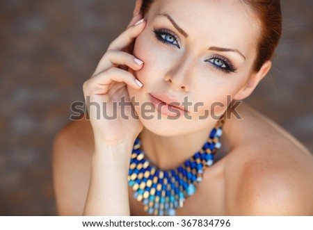 magnificent portrait of a beautiful young woman with perfect skin closeup. Portrait close up of young beautiful woman in jewellery.   - stock photo