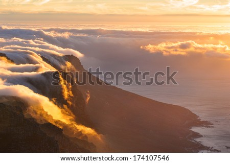 Magnificent view of Table Mountain top covered in clouds in sunset - stock photo