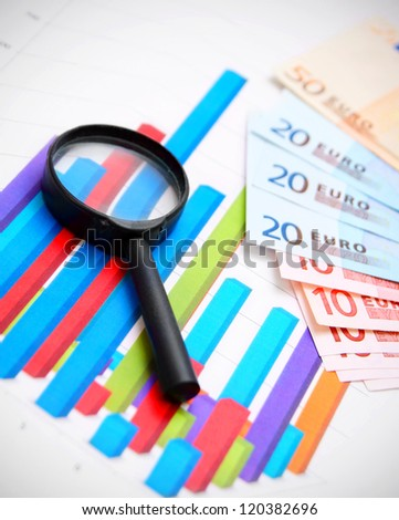 Magnifier and banknote euro on graphs. - stock photo