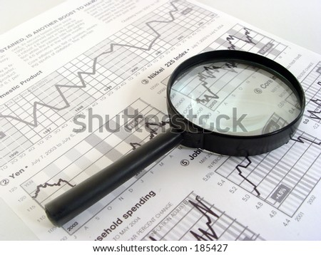 magnifier and economy newspaper - stock photo