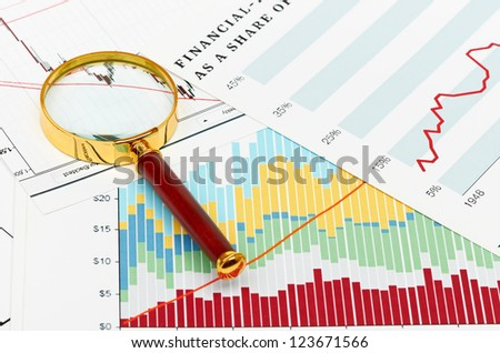 Magnifier on graphs. - stock photo