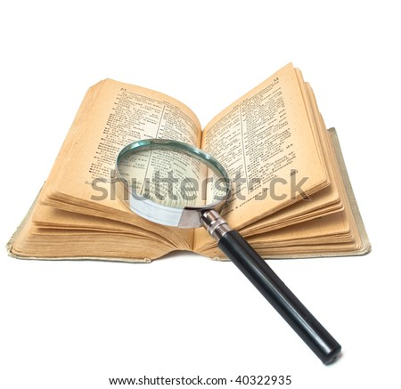magnifier on opened book - stock photo