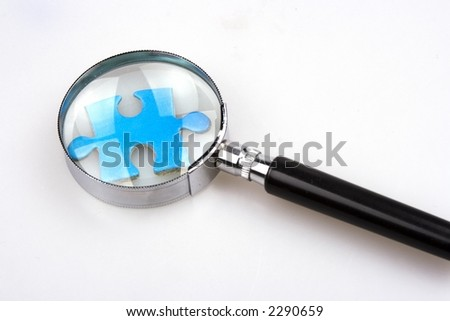 Magnifier over a piece of jigsaw puzzle. - stock photo