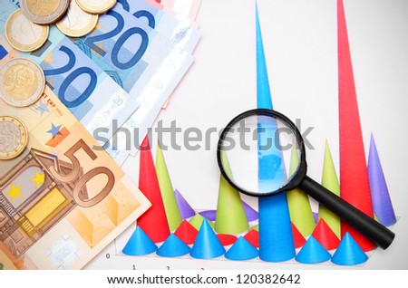 Magnifiers and money on graphs. - stock photo