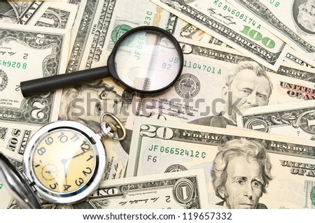 Magnifiers and watch on money. - stock photo