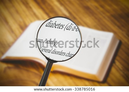 magnifying glass against bible on wooden flooring - stock photo
