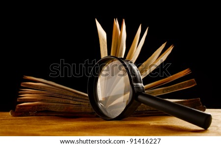 Magnifying glass and a book - stock photo