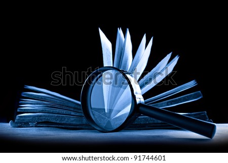 Magnifying glass and a book in blue - stock photo