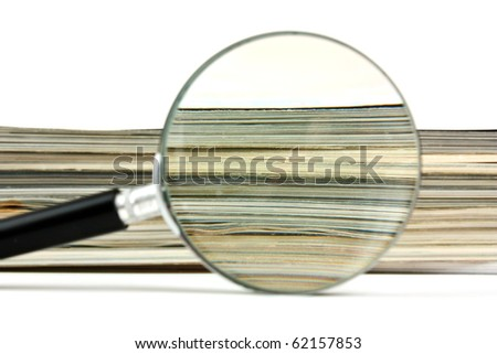 magnifying glass and a stack of magazines - stock photo