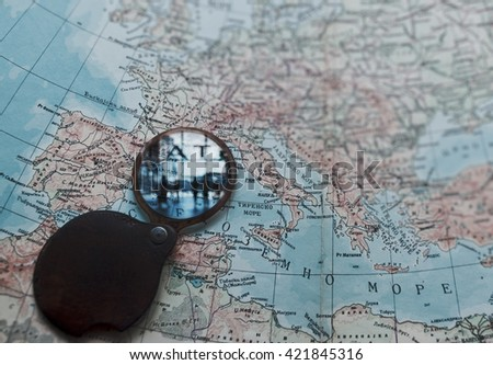 Magnifying glass and ancient old map, business people - stock photo