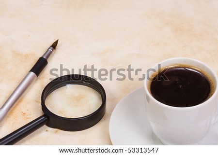 magnifying glass and coffee at texture - stock photo