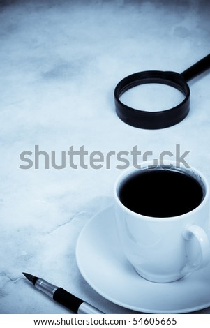 magnifying glass and coffee in blue tint - stock photo