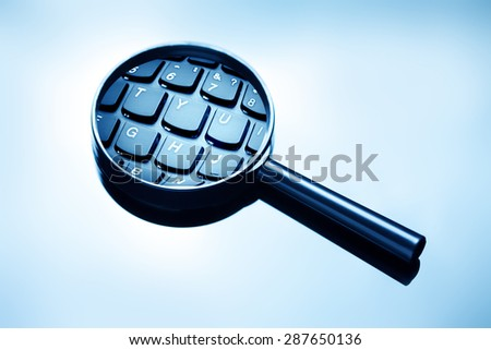 Magnifying glass and computer keyboard. - stock photo