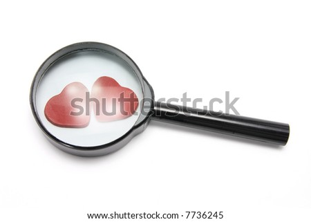 Magnifying Glass and Love Hearts on White Background - stock photo