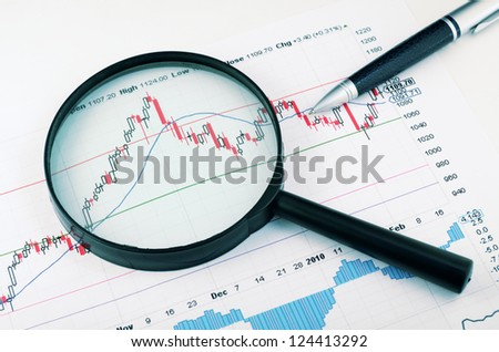 magnifying glass and pen over graph - stock photo