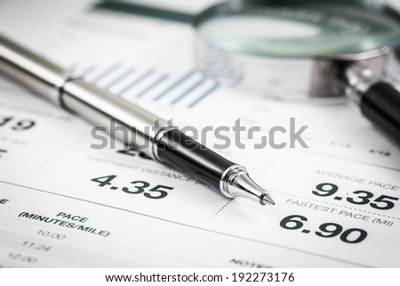 magnifying glass and pen over graph on table