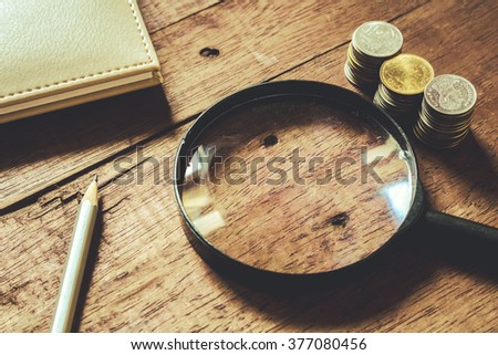 Magnifying glass and pile of coins - stock photo