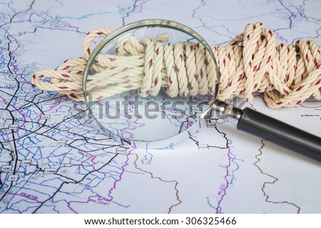 magnifying glass and rope on a map - stock photo
