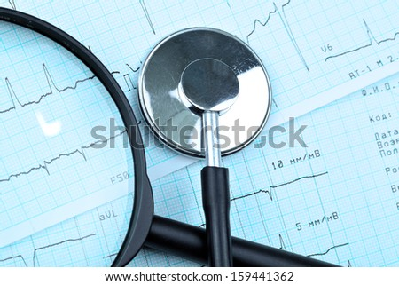 magnifying glass and stethoscope ea ECG. - stock photo
