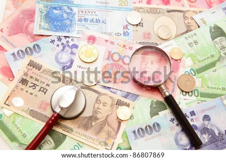 magnifying glass and  stethoscope with background of asian currency (include Korean Won, Taiwan dollar, Chinese Money yuan , Hong Kong Dollar, japanese Yen),  for finance concept - stock photo