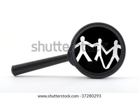 magnifying glass and team of paper man showing teamwork - stock photo