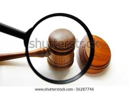 magnifying glass examining a judges court gavel (seek justice) - stock photo