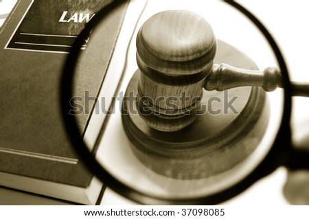 magnifying glass examining a judges court gavel, with law book - stock photo