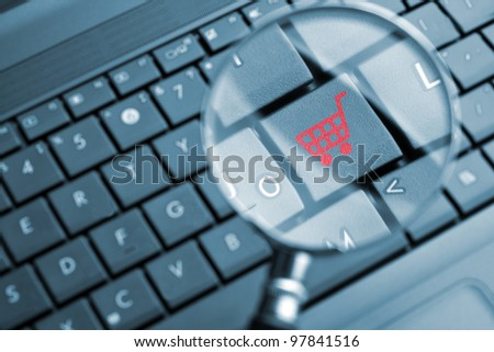 Magnifying glass focused on shopping cart icon - stock photo