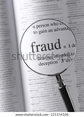 Magnifying Glass Highlighting Fraud - stock photo