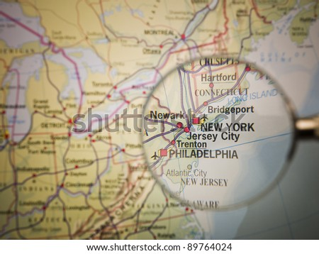 Magnifying Glass in front of a New York map - stock photo