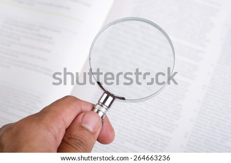 Magnifying glass in hand and blur text  - stock photo